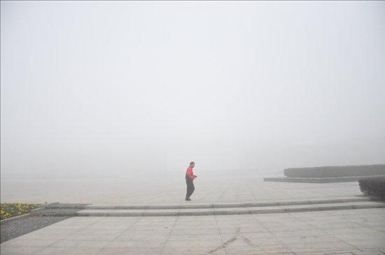 安庆 湖心北路/一位戴着口罩的市民路过湖心北路。