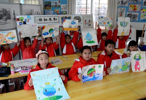 小学生们正在展示自己保护水资源主题绘画-中国娃主题墙 中国梦小学